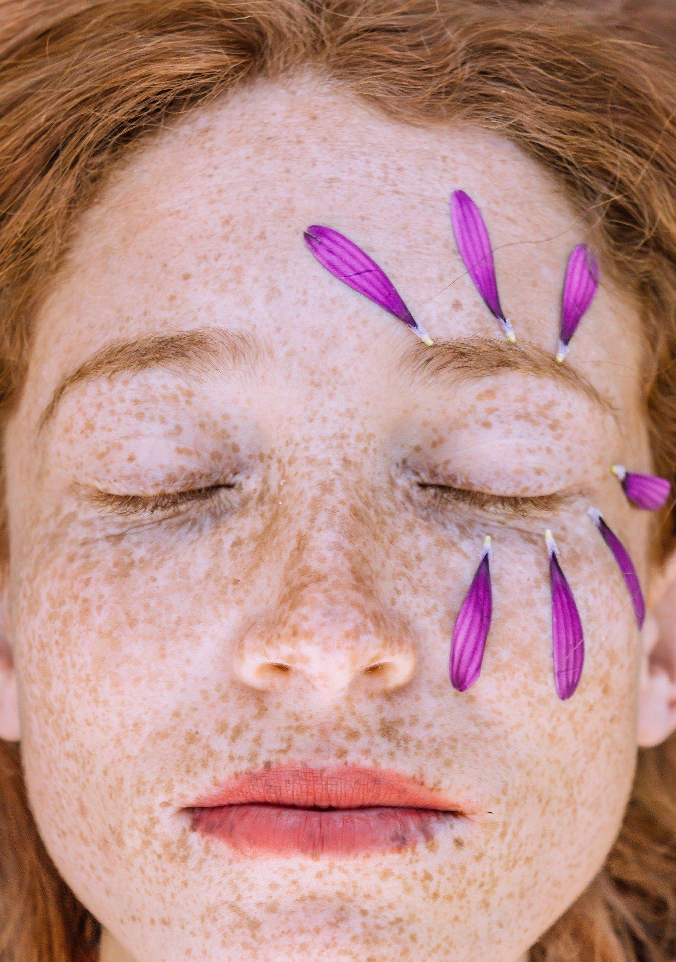 rostro con pétalos -Después de la exposición al sol... ¿after sun o crema hidratante? - Farmacia Ciudad Alta